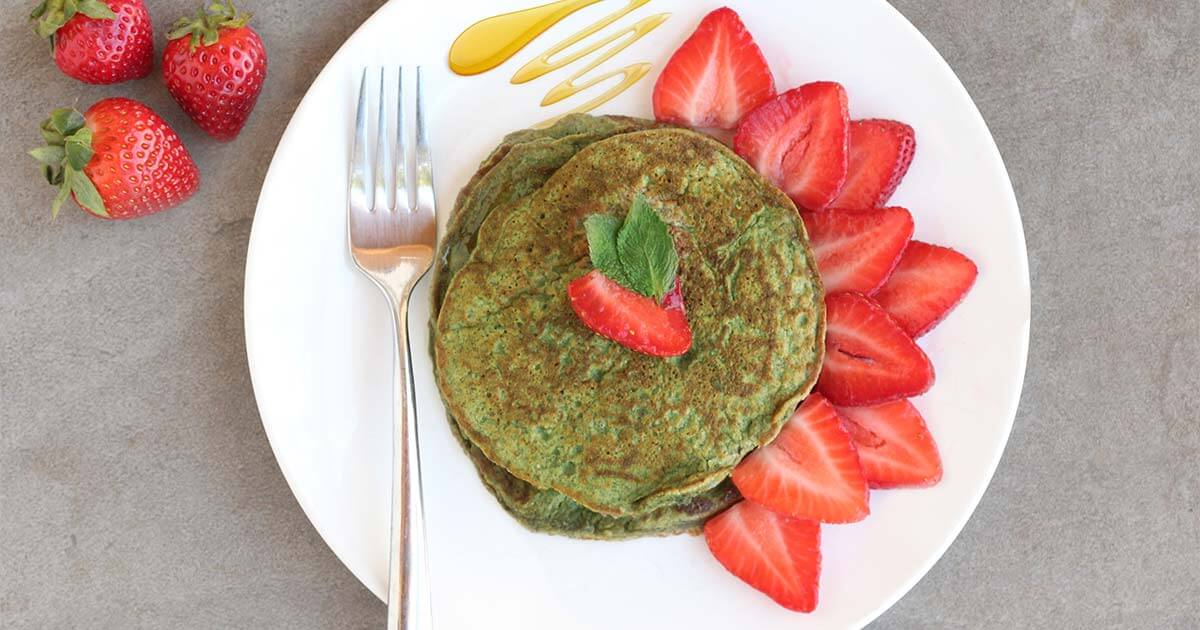 Green protein powder pancakes with strawberries